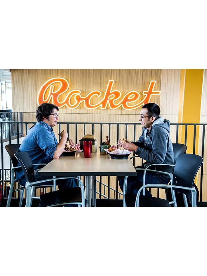 Students dining in new Rocket Grill, with old Rocket sign on the wall.