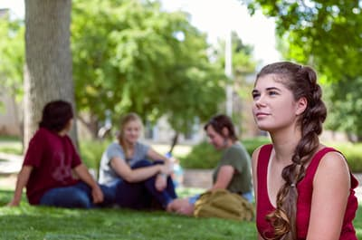 FLC student sitting on campus near other students looking wistfully off camera
