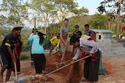 FLC Engineering major and local residents in Myanmar working on a water systems project