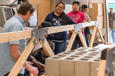 FLC Engineering majors working on a project to build a load-bearing truss bridge
