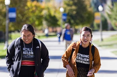 Two Native students walking across campus in tee shirts that read: strong, resilient, indigenous