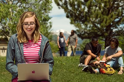 FLC student on her laptop outside on campus