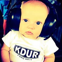A baby wearing a KDUR tee shirt and big headphones