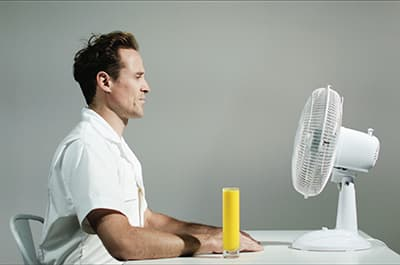 Image of a white man sitting at a desk with a glass of orange juice and a fan blowing in his face