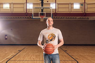 Man standing on basketball court holding ball