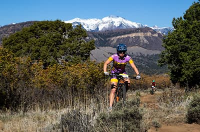 Woman on the cycling team riding her mountain bike
