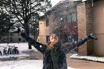FLC student playing in the snow on campus