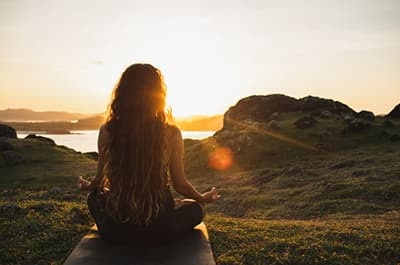 Woman meditating cross-legged at sunset in some beautiful seaside landscape