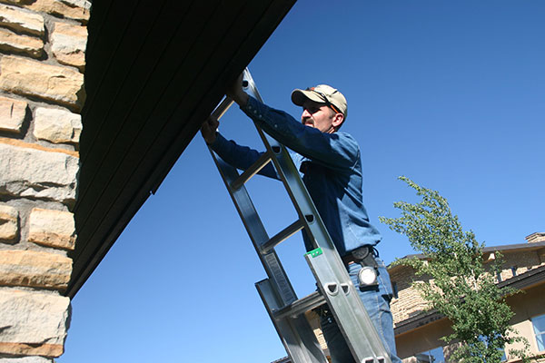 man on ladder looking at roof
